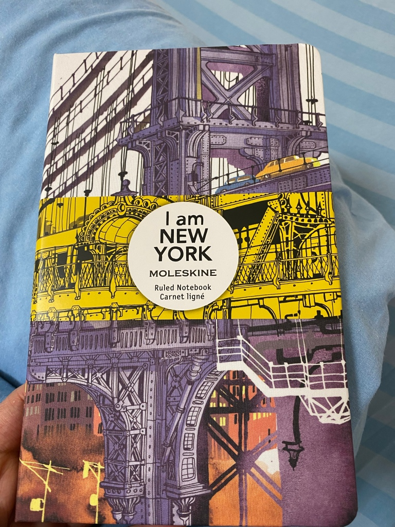 Brooklyn Bridge illustration on the front cover of the notebook, with yellow band on.