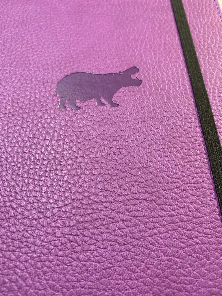 Hippo debossing on a purple faux leather, textured cover.
