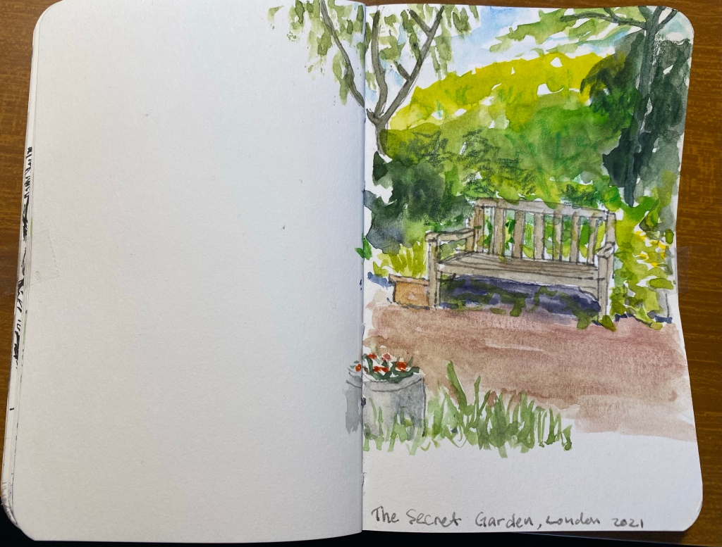 Watercolour sketch of a bench nestled in greenery at the side of a reddish path.