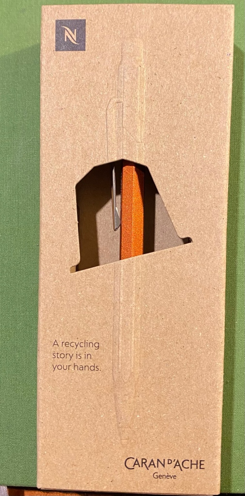 The front of the Caran d'Ache Nespresso Fixpencil box. A recycled cardboard box, in light brown, set on a green background. There's a cutout in the box that shows the orange coloured Fixpencil.